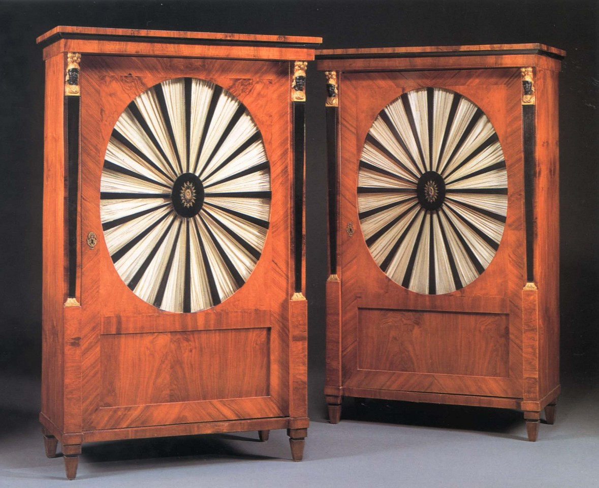19th Century AUSTRIAN ,   Pair of Biedermeier Gilt-Metal-Mounted Black Walnut, Ebonized and Parcel Gilt Cabinets  ,  1800-1825     Mixed woods ,  66 1/2 x 40 1/8 x 21 in. (168.9 x 101.9 x 53.3 cm)     Each with a molded cornice above the cabinet door centered by an oval, glazed panel with radiating ebonized splats centered by a pierced oval mount opening to reveal shelves, flanked by military terminal supports raised on square tapering feet, now fitted with silk fabric.     BIE-002-FU